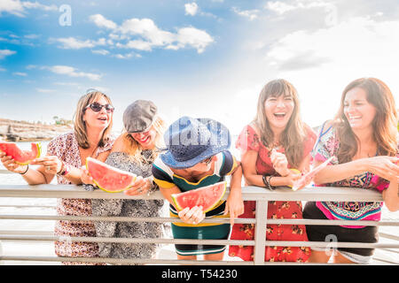 Group of people young caucasian women together having fun in a summer dy of holiday vacation together in friendship eating red watermelon and laughing - Stock Image