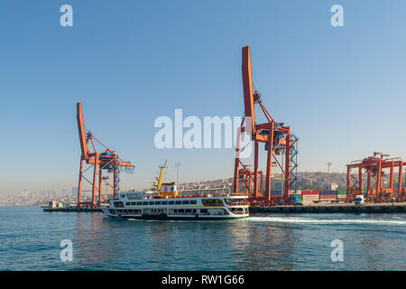 Day shot of the cranes in the shipyard of the Port of Haydarpasha, and passing ferry boat with city view in the background, Istanbul, Turkey - Stock Image