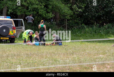 Injured mud runner being attended by a medic - Stock Image