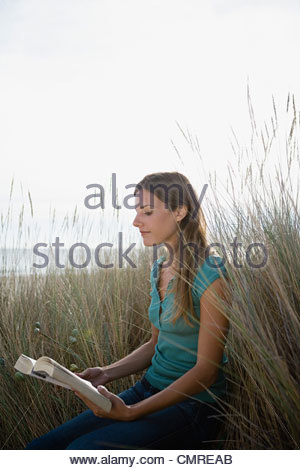 Woman reading on dune - Stock Image