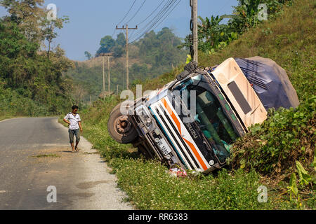 A large rigid goods truck lorry crashed into road side ditch on straight road. - Stock Image