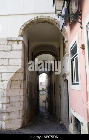 Narrow and sloped cobblestone street under a tall archway in Alfama disctrict, the most famous and ancient typical neighborhood of Lisbon. Portugal. - Stock Image