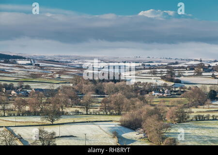 North Pennines AONB landscape, view from Whistle Crag over Teesdale into Lunedale with snow covered hills in the distance in bright winter sunshine - Stock Image