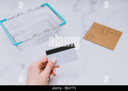woman's hand holding payment card next to empty shopping basket and mini cardboard delivery parcel, concept of shopping online - Stock Image