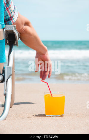 closeup of a young caucasian man relaxing on the beach, sitting on a deck chair next to a glass with a refreshing orange drink placed on the sand, wit - Stock Image