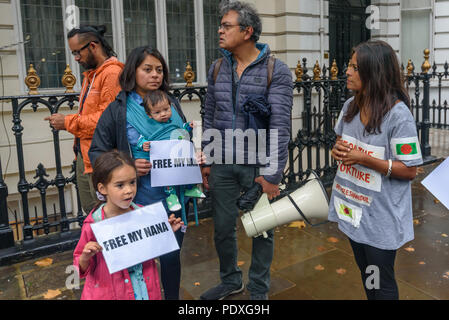 London, UK. 10th August 2018. Two young protesters with posters 'Free My Nana' (Grandad) outside the Bangladesh High Commission in London. Campaigners including a number of his relatives and several well-known photographers, called for the immediate release of Shahidul Alam, seized from his house by police on Sunday shortly after he gave an interview to Al Jazeera over Skype on the road safety protests in Bangladesh. Arrested for making comments which criticised the government, he was badly beaten before appearing in court, where a judge ordered him to be taken to hospital, but he was taken ba - Stock Image