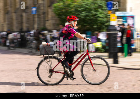 A female cyclist cycles along Kings Parade on a sunny Summer afternoon, Cambridge. UK - Stock Image
