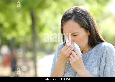 Woman sneezing using a wipe standing outdoors in a park - Stock Image