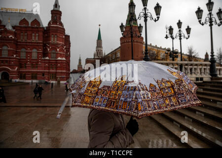 A woman goes under an umbrella in a rain on Manezh square on the background of the Moscow Kremlin in downtown of Moscow, Russia - Stock Image