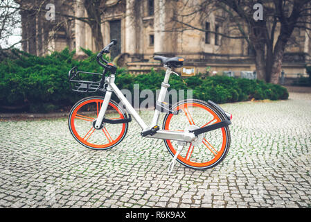 City bike parked on sidewalk in the park. Bike sharing service. Modern bicycle on the city street. Vintage photo - Stock Image