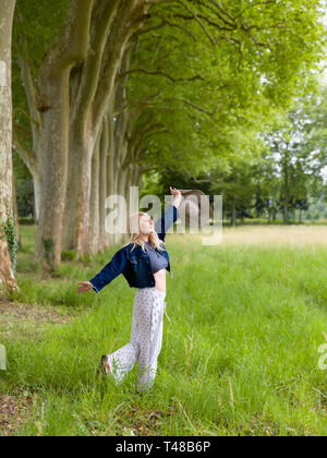 Beautiful young blonde woman dancing in the countryside in summertime - Stock Image