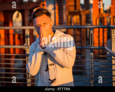 Amazed handsome man looking at camera outdoors  - Stock Image