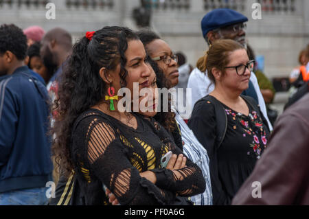 London, UK. 18th August 2018. A woman in the crowd wears Rasta ankh ear rings at the annual National Memorial event in Trafalgar Square to remember and honour the victims of the African Holocaust/Transatlantic Slave Trade and promote International Slavery Remembrance Day, 23rd August. The event called for Africans to celebrate their identity and to remember their ancestors, and began with libations remembering many black heroes. ers talked about the Credit: Peter Marshall/Alamy Live News - Stock Image