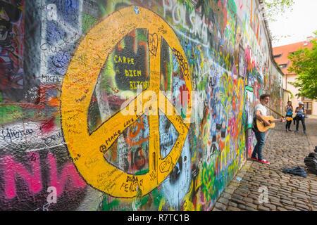 Prague John Lennon Wall, view of a busker playing a guitar alongside the John Lennon Wall in the Mala Strana district of Prague, Czech Republic. - Stock Image