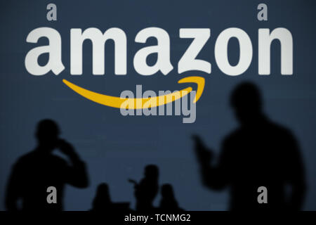 The Amazon logo is seen on an LED screen in the background while a silhouetted person uses a smartphone in the foreground (Editorial use only) - Stock Image