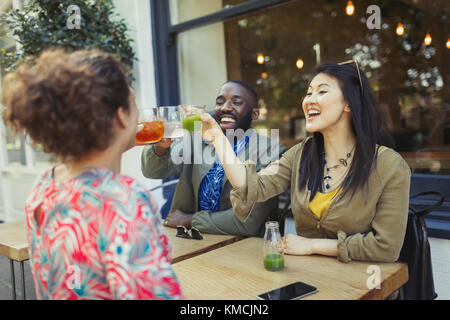 Smiling enthusiastic friends toasting fresh juice glasses at sidewalk cafe - Stock Image