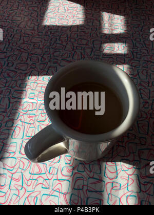 Early morning sunlight throws shadow on cup of coffee sitting on table of diner, Fargo, North Dakota - Stock Image