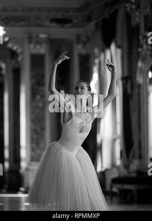 Beautiful ballerina dancing in a luxurious hall against the window. Black and white image. Closeup. - Stock Image