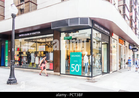 Gijon, Spain - 6th July 2018: Shoppers walk past a United Colors of Benetton shop. The store is part of a clothing chain. - Stock Image