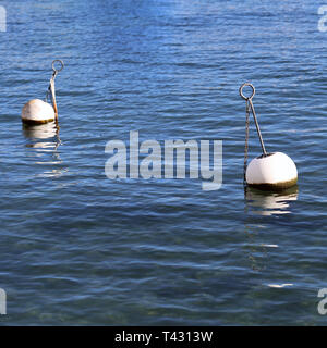 Buoys photographed in picturesque town of Nyon, Switzerland. In this photo you can see relatively calm lake and white buoys. Relaxing view! - Stock Image