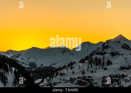 Orange skies and sun rays at sunset over the mountains in Obertauern, Austria - Stock Image