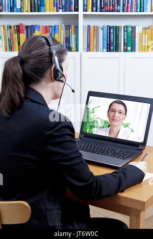 Female member of the staff department in her office with computer and headset, talking with a woman during a live video chat, teleconference concept - Stock Image