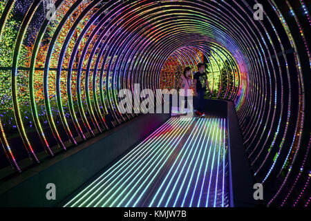 Man and woman walking in LED pathway at 'Universal Journey' at Universal Studios Singapore. - Stock Image