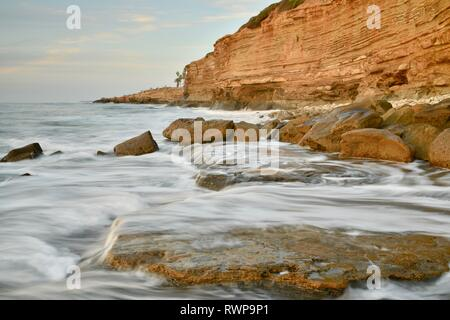 Crashing waves over rocks, with water motion of surf, gold glow on rugged cliffs at Sunset Cliffs Natural Park, Point Loma, San Diego, California, USA - Stock Image