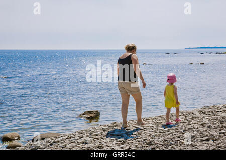 Grandmother and child walking along a pebble stone beach on Gotland, Sweden - Stock Image
