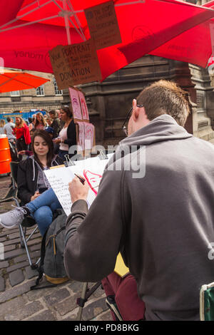 Edinburgh, Scotland, UK. 7th August 2018. Street acts and artists, alongside promoters of Fringe Festival events, ply the streets of Edinburgh Festival, providing entertainment and amusement to the many visitors to the Fringe. This ambidextrous artist produced portraits in a two minute sitting. Credit Joseph Clemson, JY News Images/Alamy. - Stock Image