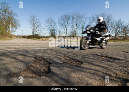 potholes in the middle of the road after a hard winter of snow. Who will pay for these pot holes to be repaired? - Stock Image