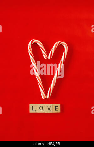 candy cane heart on red background, love in scrabble letters - Stock Image