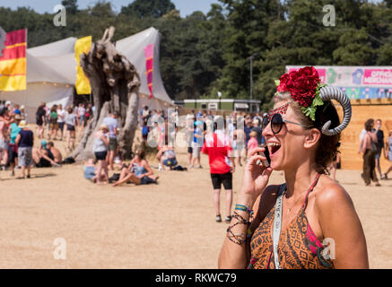 A festival goer wearing a strange hat made of a flower and a mutton horn laughs while talking on her phone. - Stock Image