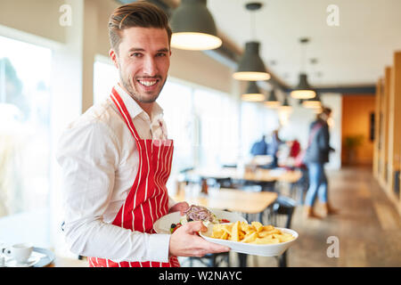 Man as a friendly waiter in training serves food in the restaurant - Stock Image