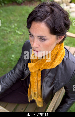 Young woman wearing leather jacket and handmade scarf - Stock Image