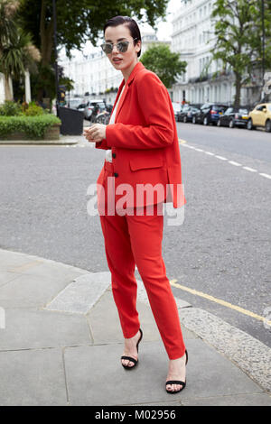 Chic woman in red suit on London street corner, full length - Stock Image