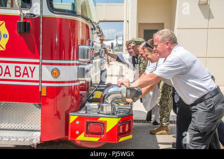"""180827-N-UR565-091 NAVAL SUPPORT ACTIVITY SOUDA BAY, Greece (August 28, 2018)  Naval Support Activity Souda Bay, Greece personnel push a new fire engine into the fire house during a """"wet down ceremony"""" at the installation fire house, August 27, 2018.  A longstanding tradition in the fire service, the """"wet-down"""", is a ceremonial process in which firefighters officially place into service a new fire apparatus by anointing it with water sprayed from the retiring unit and pushing it into the station. (Photo by Joel Diller/Released) - Stock Image"""