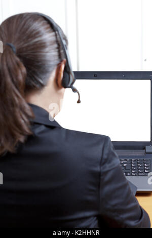 Rear view of a woman in a black blazer with headset and microphone in front of her computer, white, empty screen, video call concept template - Stock Image