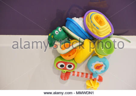 Mix of plastic toys including boats and frog on a bathtub - Stock Image