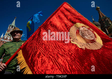 A man holding a red banner embroidered with the emblem of the USSR on Red Square in the center of Moscow during communist's party rally, Russia - Stock Image