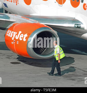 Aviation worker man in high vis jacket at work beside easyJet passenger airplane jet engine nacelle pod on tarmac at Stansted Airport Essex England UK - Stock Image