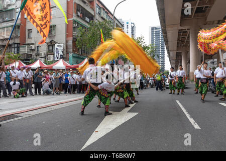 A dance troupe performs the dragon dance during a Matsu procession through the streets of Taipei in a show of practiced, living religion. - Stock Image