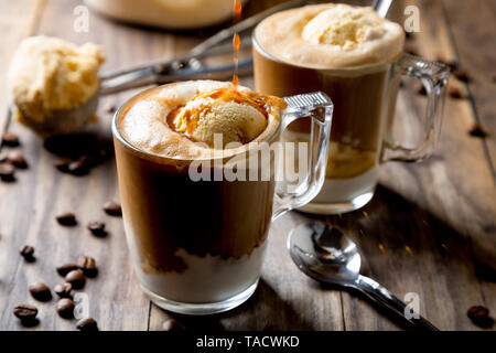 Pouring coffee on vanilla ice cream to make an affogato coffee on a rustic wooden table - Stock Image