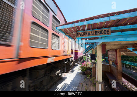 Motion-blurred train whizzes past old waiting gazibo of the Siam-Burma Railway over River Kwai in Kanchanaburi, Thailand. The infamous River Kwai brid - Stock Image