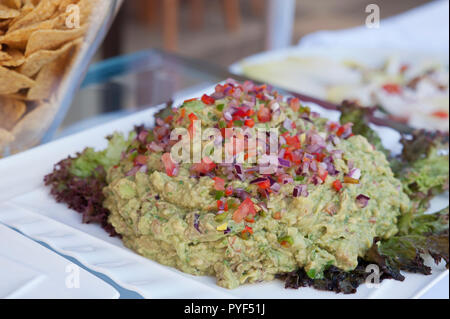 Freshly made guacamole dip on a white plate prepared for a buffet bar, or self-service restaurant, vegetarian dip for easy buffet style snacking - Stock Image