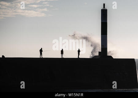 Aberystwyth, Wales, UK. Sunday 30 Jun 2019.  UK weather:  People fishing near the harbour lighthouse in Aberystwyth get sprayed by the waves on a breezy and cool evening on the west coast of wales. Temperatures have fallen sharply from the record breaking highs of recent days  Photo credit Keith Morris/Alamy Live News - Stock Image