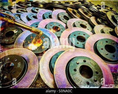 Destroying brake discs by burning and cutting - Stock Image