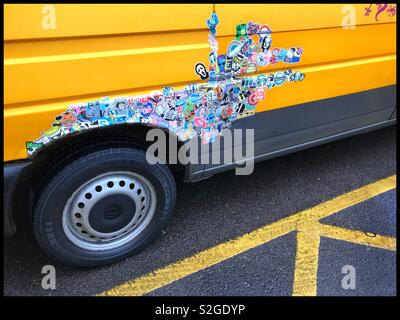 Lots of small picture stickers one atop the other and above the wheel arch of a van. Is it adverting? Is it a political statement? Is it just to patch up some rust? Yellow is the predominant colour. - Stock Image