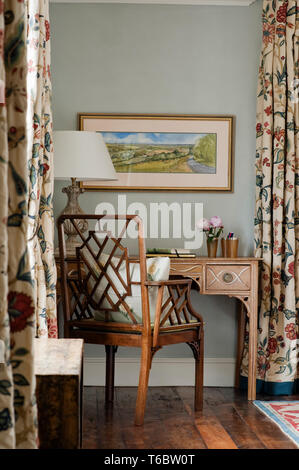 Wooden chair and desk with artwork on wall - Stock Image