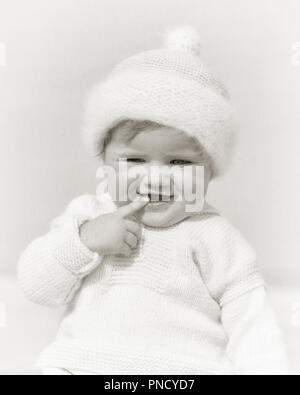 1920s SQUINTING SMILING BABY GIRL WEARING KNIT WHITE WOOL HAT AND SWEATER INDEX FINGER ON LIPS LOOKING AT CAMERA - b1976 HAR001 HARS WOOL HALF-LENGTH EXPRESSIONS B&W KNIT EYE CONTACT INDEX HAPPINESS AND SQUINTING AT STYLISH DARLING GROWTH JUVENILES BABY GIRL BLACK AND WHITE CAUCASIAN ETHNICITY HAR001 OLD FASHIONED - Stock Image